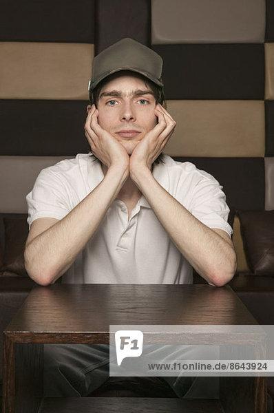 Porträt eines traurigen Mannes  der an einem Tisch sitzt.