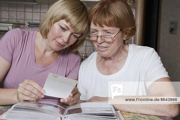Mutter und Tochter beim Betrachten von Fotos