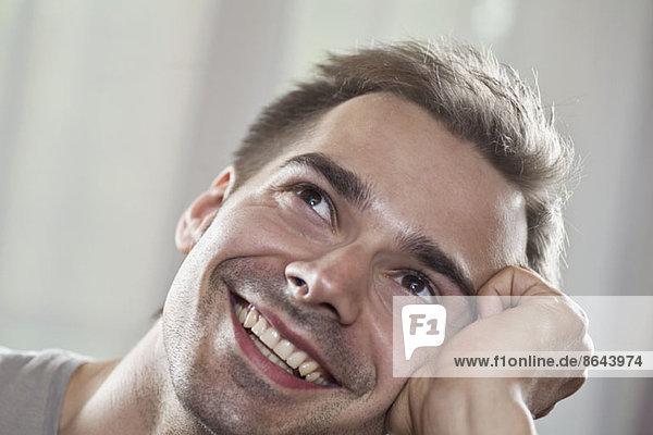 Junger Mann schaut auf und lächelt  Nahaufnahme