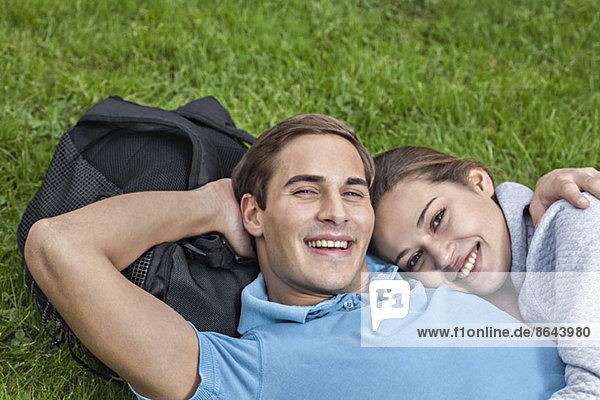Portrait eines jungen Paares auf Gras liegend