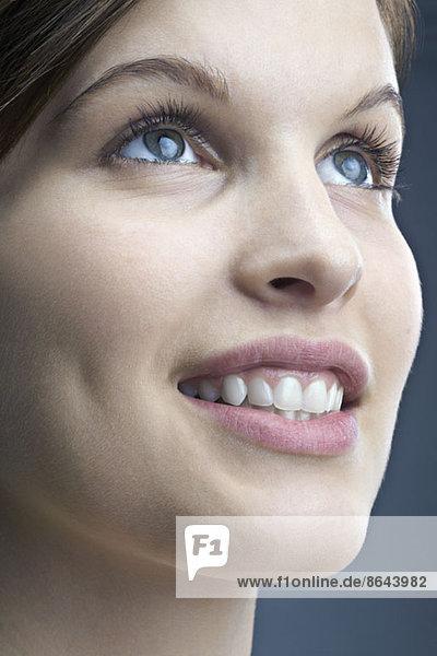 Junge Frau schaut auf und lächelt  Nahaufnahme