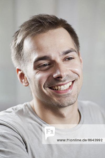 Junger Mann schaut weg und lächelt  Nahaufnahme