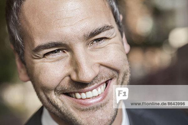 Mittlerer erwachsener Mann  der wegschaut und lächelt  Nahaufnahme