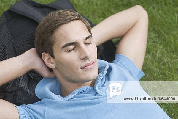 Junger Mann ruht auf Gras