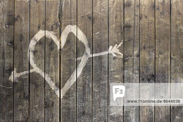Herzform mit Pfeilsymbol auf Holzzaun