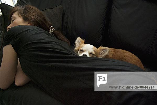 A woman with dog sleeping on a sofa