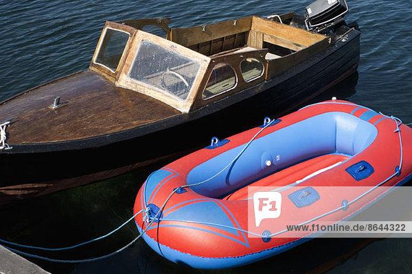 Ein Retro-Motorboot liegt neben einem neuen Schlauchboot.