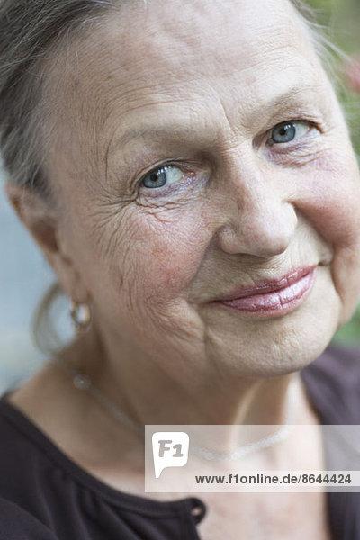Ältere Frau schaut weg  lächelnd