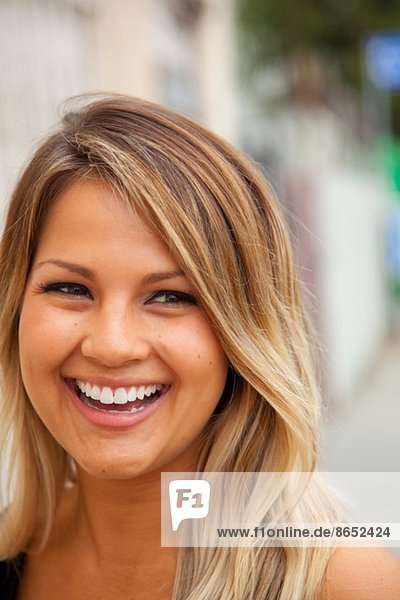 Porträt einer jungen Frau mit blonden Haaren  die lächelt