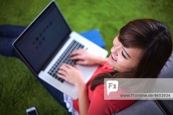 Junge Frau sitzt auf einem Teppich und tippt auf einem Laptop.