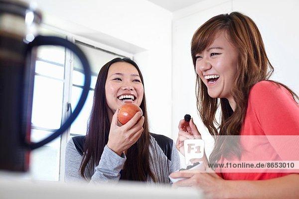 Zwei junge Frauen in der Küche beim Obstessen
