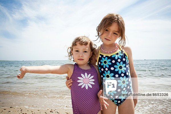 Portrait of two young sisters on beach at Falmouth  Massachusetts  USA