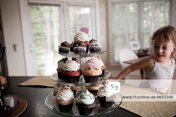 Weibliches Kleinkind schaut auf den Kuchenstand voller Muffins.