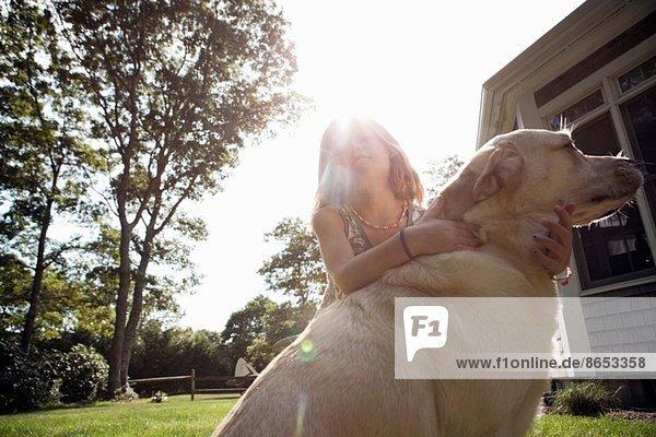 Junges Mädchen umarmt Haustier Labrador im Garten