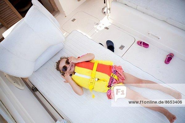 Kleinkind im Boot versteckt mit Schwimmweste und Sonnenbrille