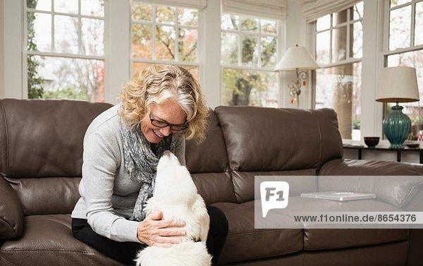 Seniorin mit Labradorhund im Wohnzimmer