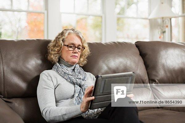 Seniorin auf dem Sofa mit Blick auf das digitale Tablett
