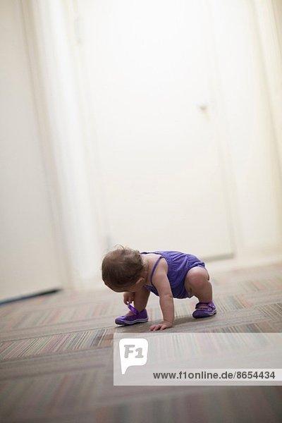 Kleinkind auf dem Boden kauerndes Mädchen