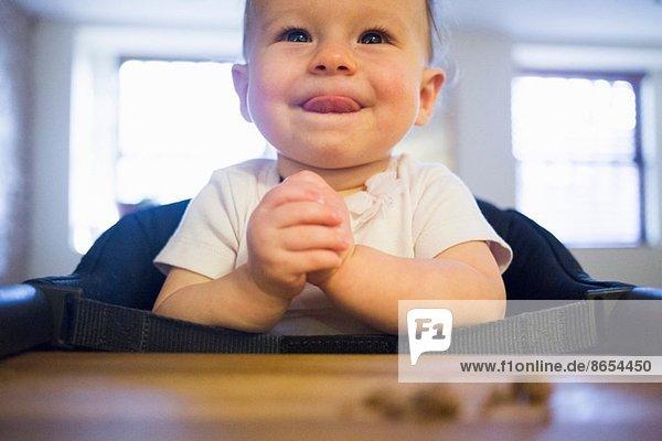 Toddler girl licking lips in highchair