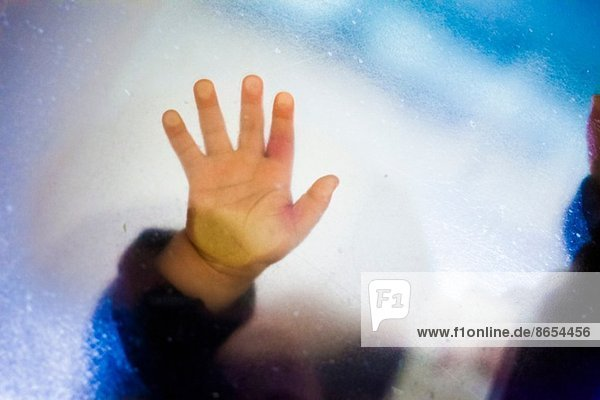 Toddler girl's hand touching glass