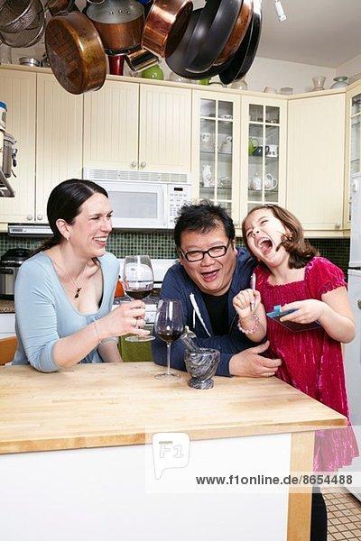 Reife Paare in der Küche lachend mit kleiner Tochter