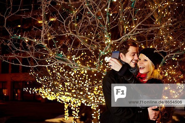 Junges Paar beim Selbstporträt mit Stadtbeleuchtung