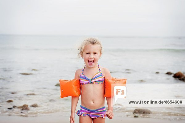 Junges Mädchen mit Armbinden am Strand