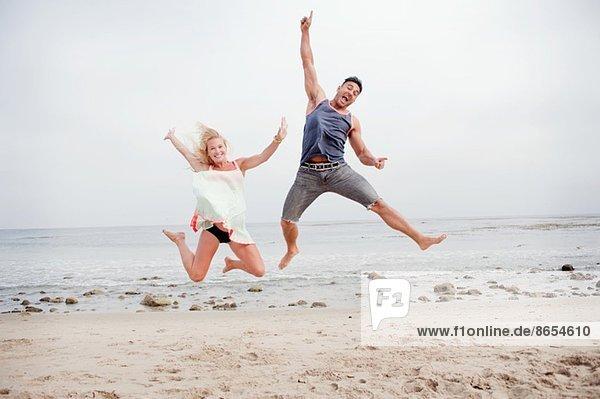 Ein schwangeres Paar springt in der Luft am Strand.
