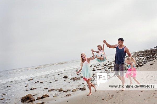 Eltern und zwei junge Mädchen beim Spaziergang am Strand