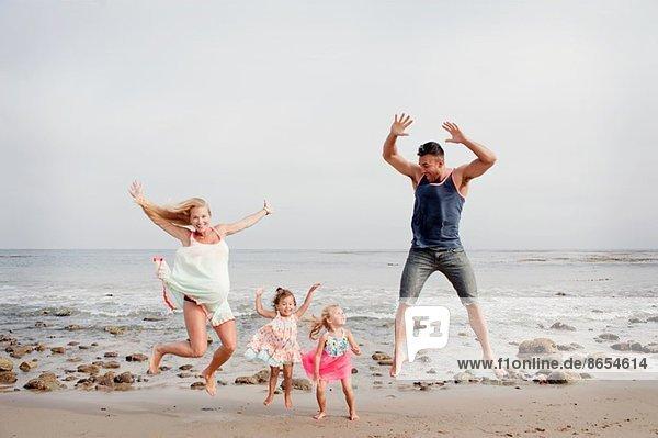 Eltern und zwei junge Mädchen beim Springen am Strand
