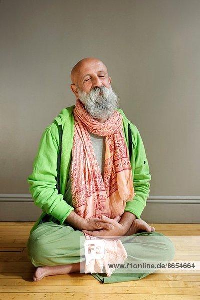 Porträt eines älteren Mannes  der in Lotusstellung auf dem Boden sitzt.