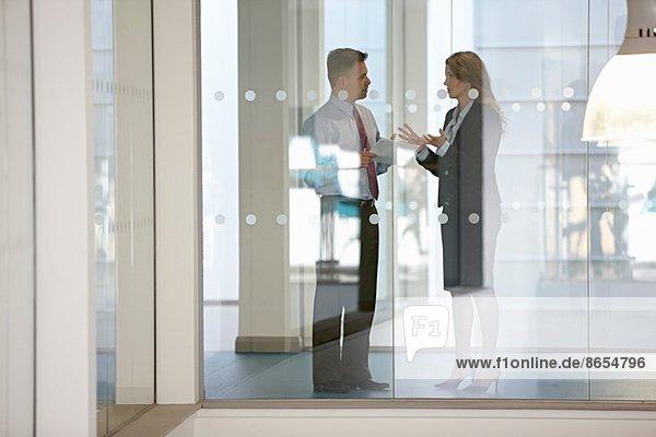 Geschäftskollegen im Gespräch durch Glas