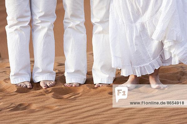 Familie in weißer Kleidung  barfuß im Sand stehend  niedriger Schnitt