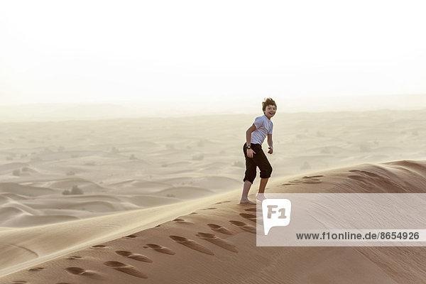 Teenager-Junge läuft auf Wüstendüne