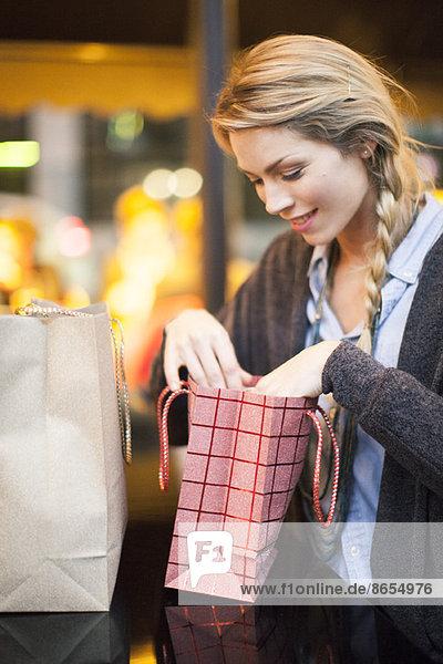 Zufriedene Käuferin bei der Prüfung ihrer Einkäufe Zufriedene Käuferin bei der Prüfung ihrer Einkäufe
