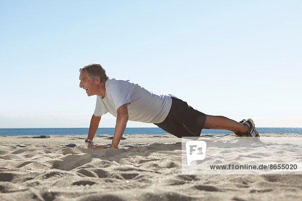 Senior man doing push ups on beach
