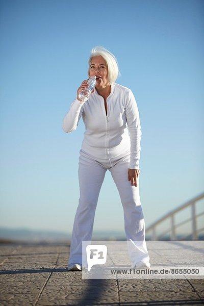 Mature woman drinking water on walk
