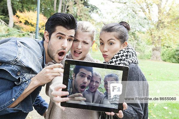 Freunde fotografieren sich selbst und machen lustige Gesichter mit einem digitalen Tablett im Freien.