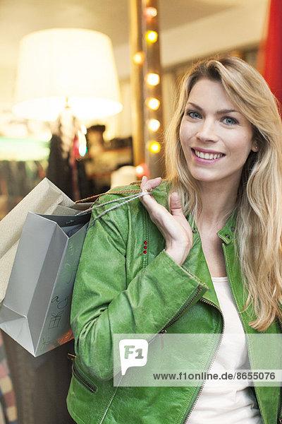 Frau trägt Einkaufstaschen über die Schulter
