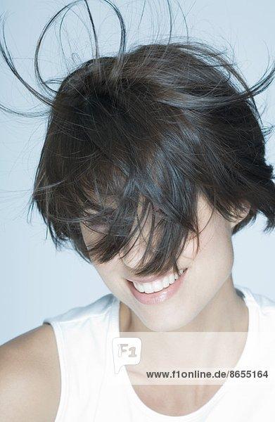 Frau mit Haaren vor dem Gesicht  lächelnd  Portrait