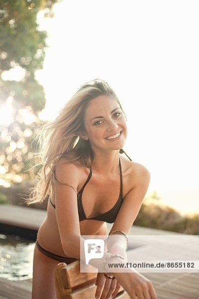 Frau im Bikini posiert am Pool