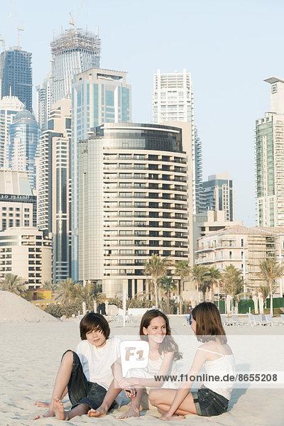 Geschwister sitzen zusammen am Strand  Dubai  Vereinigte Arabische Emirate