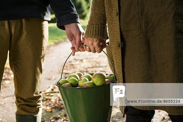Paar tragende Eimer mit Äpfeln