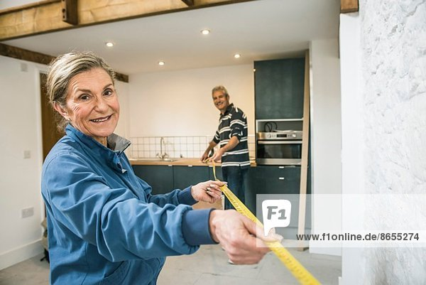 Senior couple doing DIY  using measuring tape