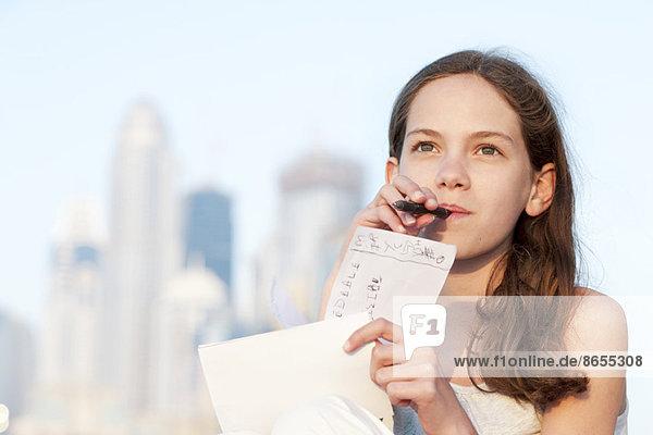Preteen Mädchen sitzen im Freien mit Stift im Mund  Blick nach oben in Gedanken