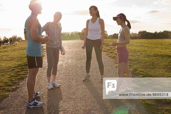 Personal Trainer mit einer Gruppe von Kunden  die sich auf den Lauf vorbereiten.