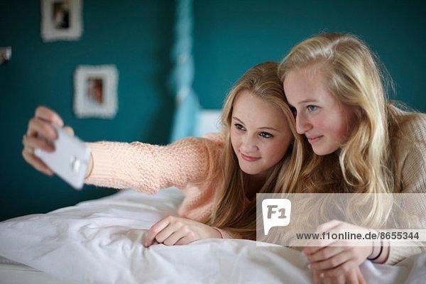 Two teenage girls taking selfie in bedroom