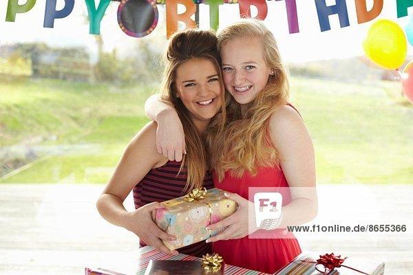 Teenage girl and friend with birthday gift