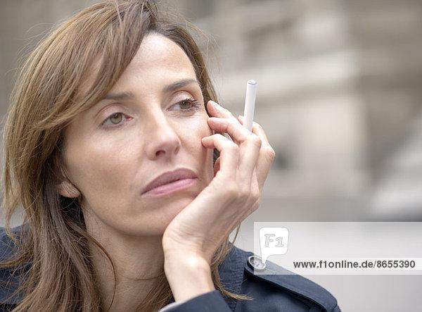 Frau raucht elektronische Zigarette im Freien