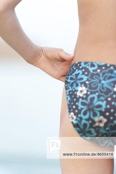 Mädchen im Bikini stehend mit der Hand auf der Hüfte  abgeschnittene Rückansicht